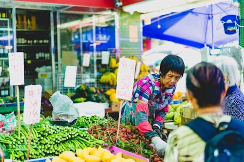 Pazarda turp ve sebze tutan pembe ve mavi ceket giyen kadın