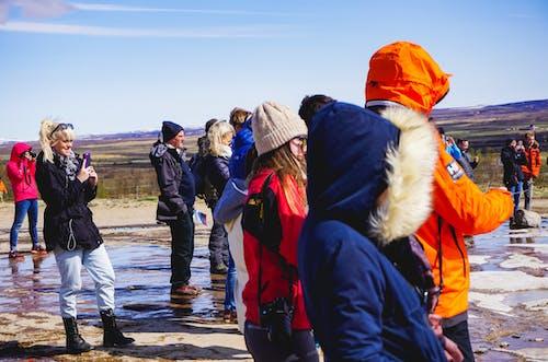 Şapkalı ve ceketli turistler İzlanda'daki bir kaplıcanın fotoğraflarını çekiyor