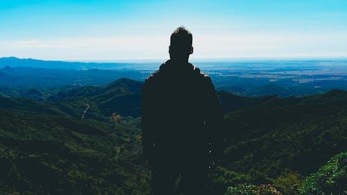 Tepelerde aşağıda dolambaçlı yollar ile mavi dağlara bakan adam