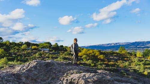 Las Sierras Arjantin'deki Mina Clavero'da bir yürüyüşte altın saatte bir kayanın tepesinde duran kız