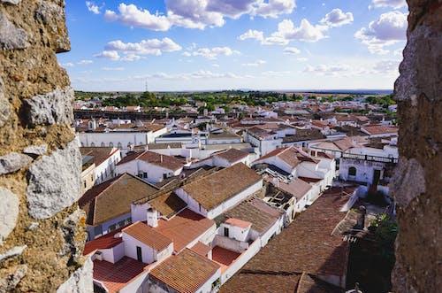 Portekizli bir köyde kırmızı kiremitli çatıların üzerinde beyaz bulutlarla noktalı mavi gökyüzü
