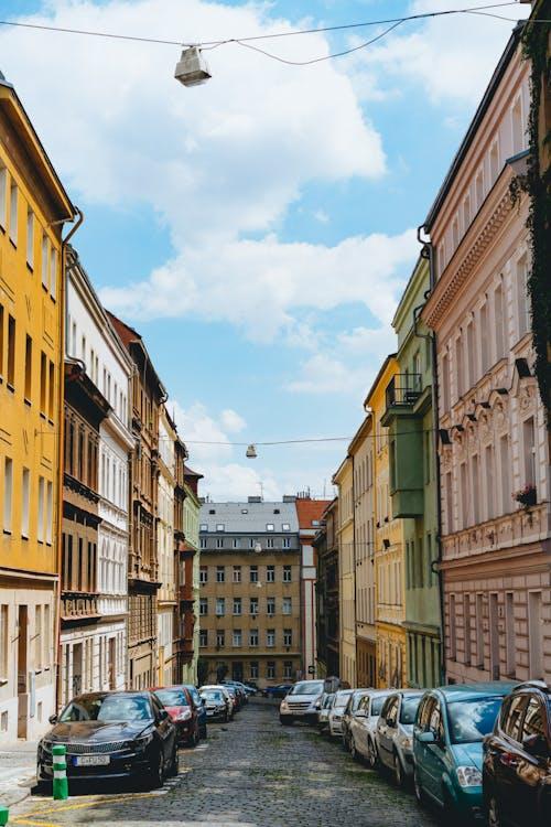 Prag'da mavi berrak bir gökyüzü olan Arnavut kaldırımlı bir sokakta pastel renkli uzun pencereli binalar