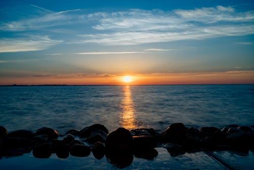 Büyük taşlardan oluşan bir çizgi ile karanlık bir denize karşı parlayan turuncu ve mavi gün batımı
