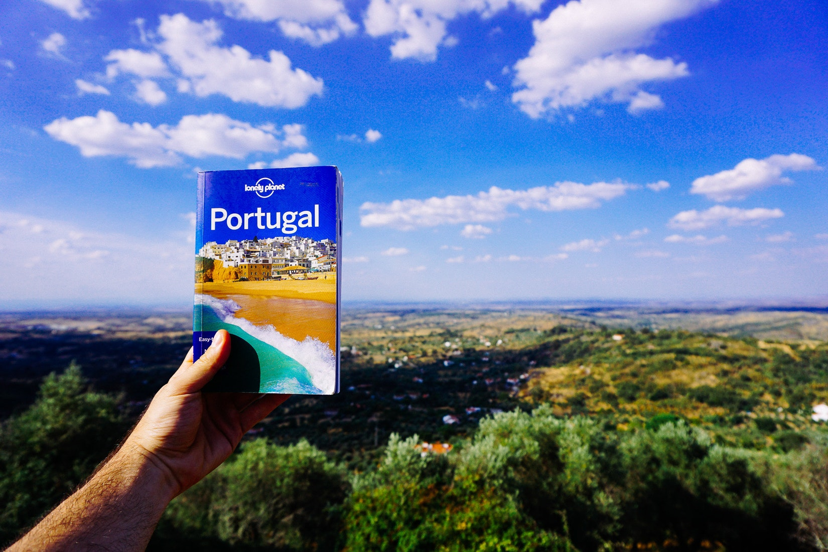 Using a book and a map to read directions for tourism in Portugal