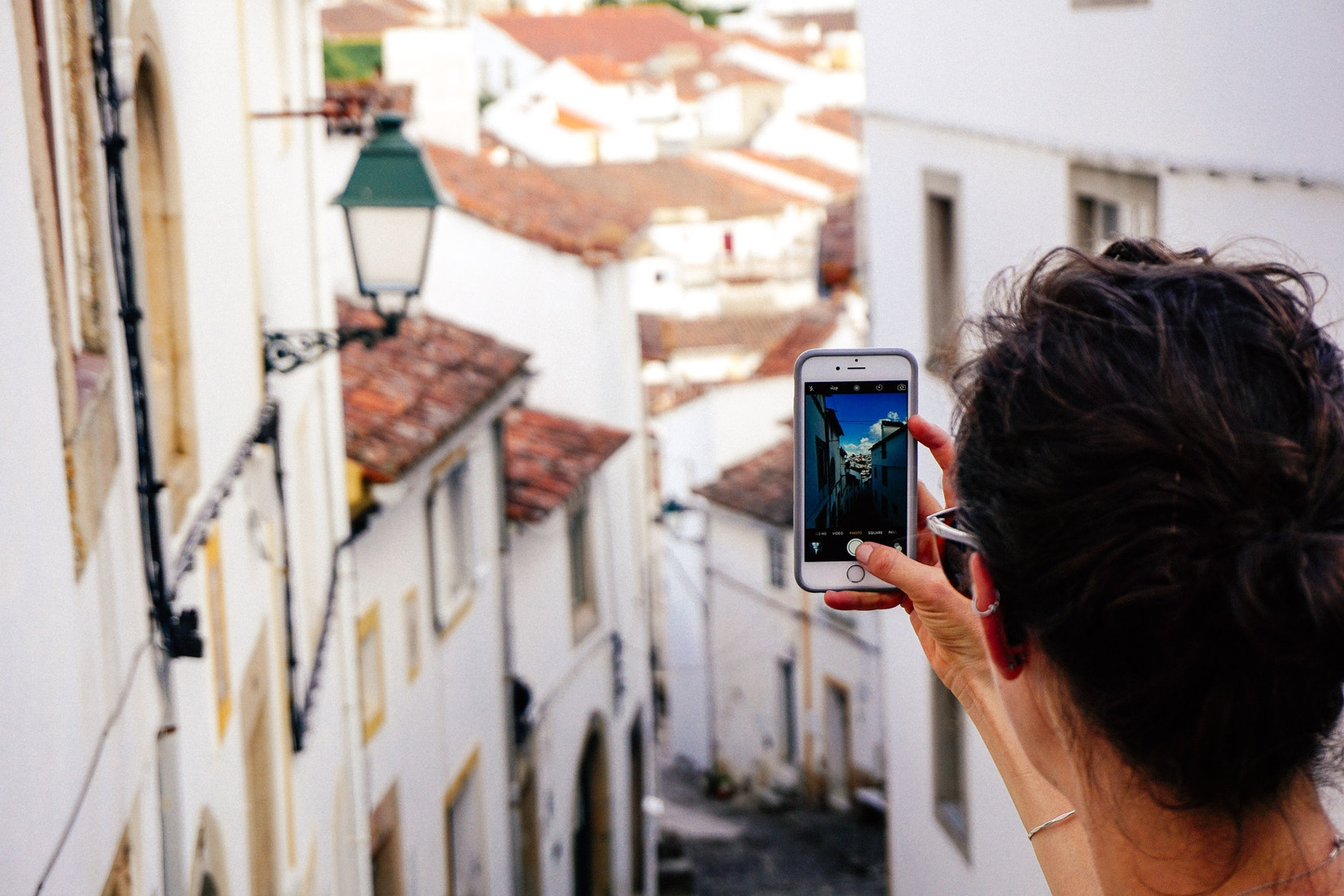 Girl holding up a cell phone to take a photo of depth in a Portuguese village of white houses