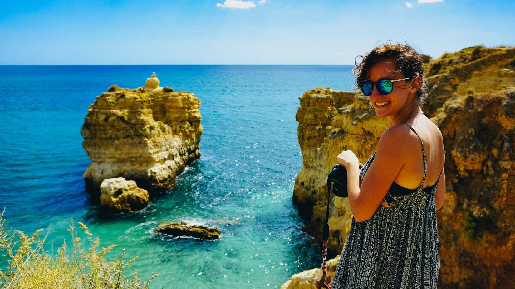 A girl with turquoise and blue waters at a sandy beach with rock formations in Portugal