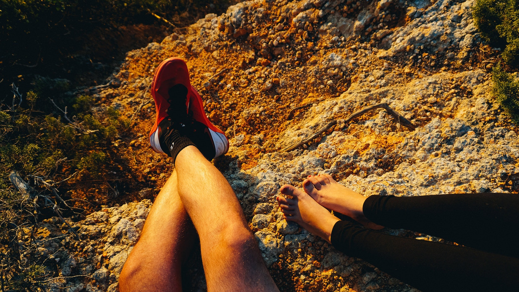 Feet of girl and guy against rocks during sunset hour at cliffs
