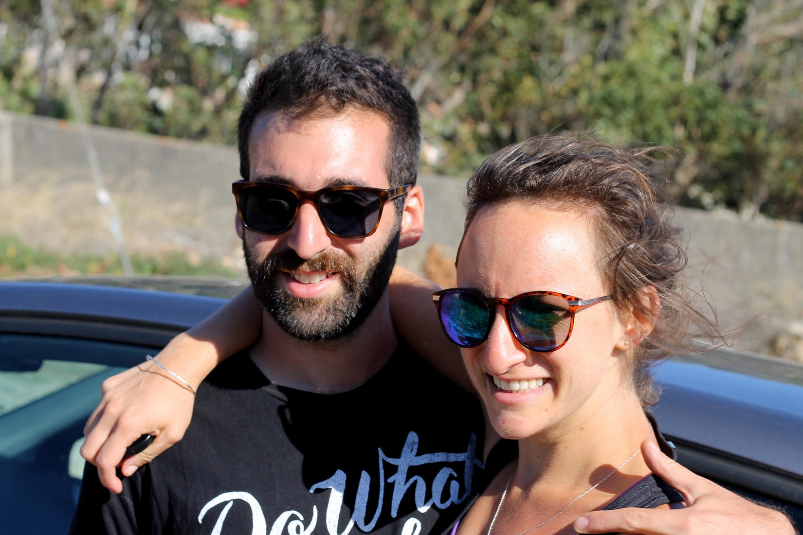 Boyfriend and girlfriend wearings sunglasses on a sunny day in Portugal after a hike