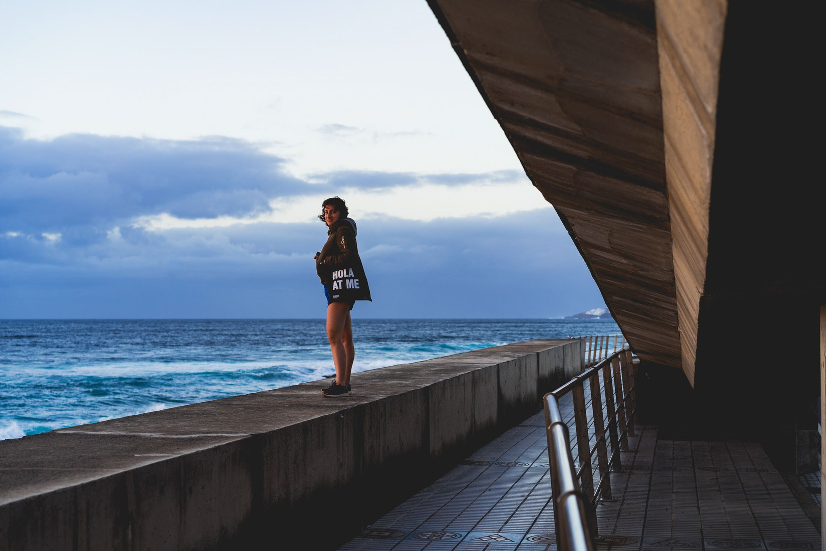 Girl standing on a ledge by the ocean