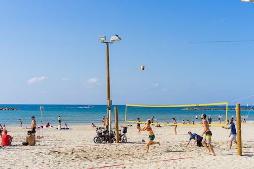 Tel Aviv'de bir plajda voleybol oynayan insanlar