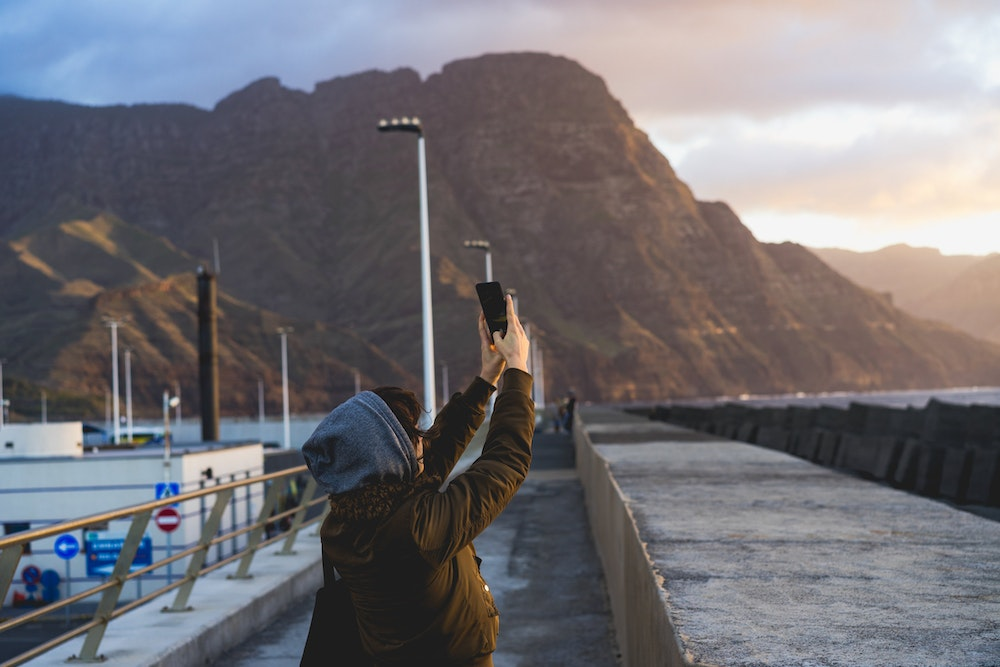 Becca taking a photo of the sunset in Puerto de las Nieves