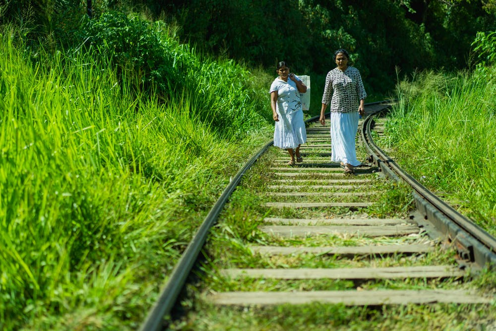 People walking on train tracks in Sri Lanka