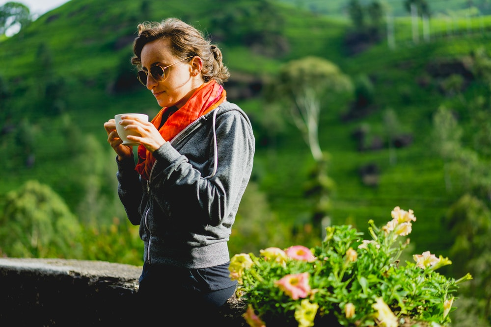 Girl drinking tea with green hills at Mackwoods