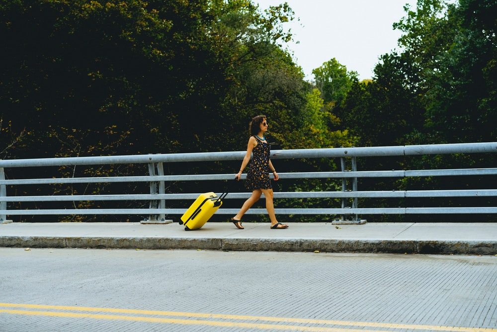 Becca walking in Beacon, New York with an away luggage suitcase